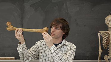 "A student examines a femur for Anthro 43, ""Human Osteology.&qu"