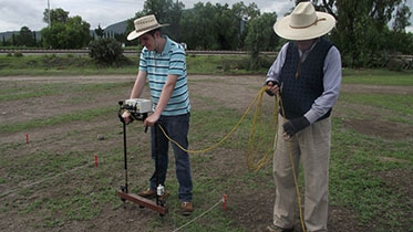Andres Mejia-Ramon '16 and Professor Luis Barba, an archeologist and geophysicist from the Universidad Nacional Autonoma de Mexico, use a ground resistivity meter to detect buried structures. (Photo by David Carballo, Boston Uni